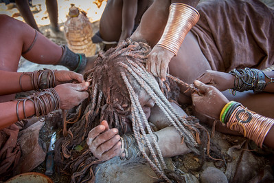Preparing a Himba woman long dreadlocks