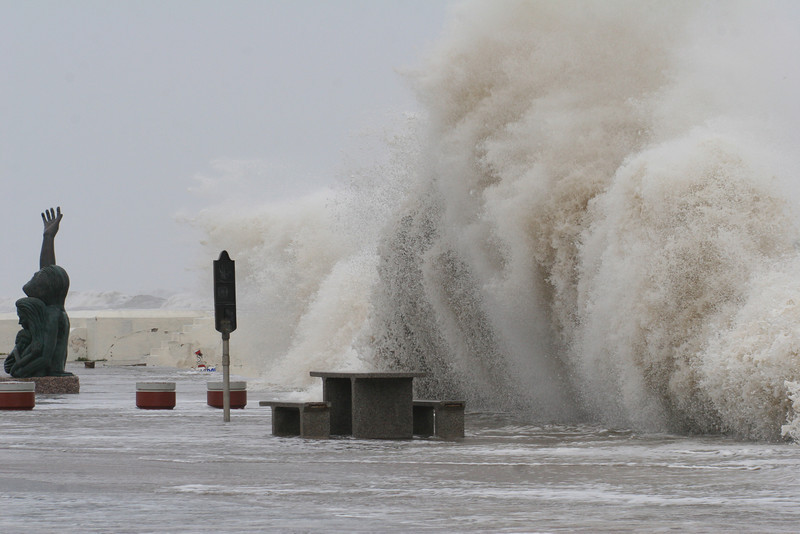 Giant waves, created in advance of Hurricane Ike in 2008, crash over the Galveston sea wall dwarfing the 10 foot tall statue that memorializes the 1900 Hurricane that killed over 6000 Galvestonians.  Ike's eye eventually came ashore over Galveston with category 3 winds killing over 100 and until Irene in 2011, was the costliest hurricane to make landfall in the United States.