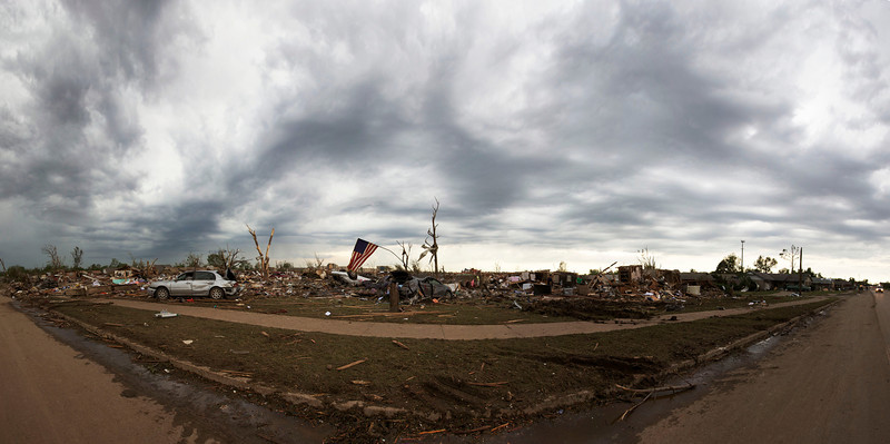 An American flag stands over the devastation in a Moore Oklahoma neighborhood created by the deadly F5 tornado that struck on May 20, 2013.
