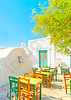 Beautiful stone made road with traditional houses and handmade tables and chairs out of a restaurant in Chora the capital of Amorgos island in Greece