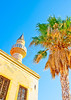 Old islamic church building with minaret tower and a palm beside in Kos island in Greece