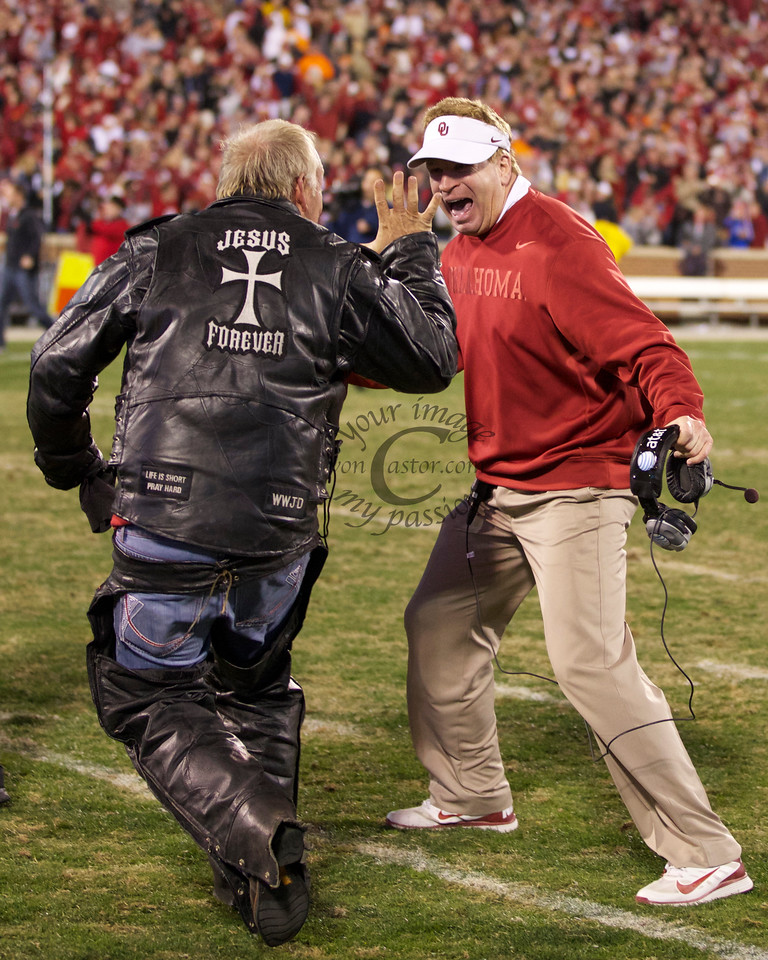 Oklahoma defensive coordinator Mike Stoops celebrates with a fan moments after OU defeated OSU in the 2012 Bedlam game in OT,  51-48 at Memorial Stadium in Norman.
