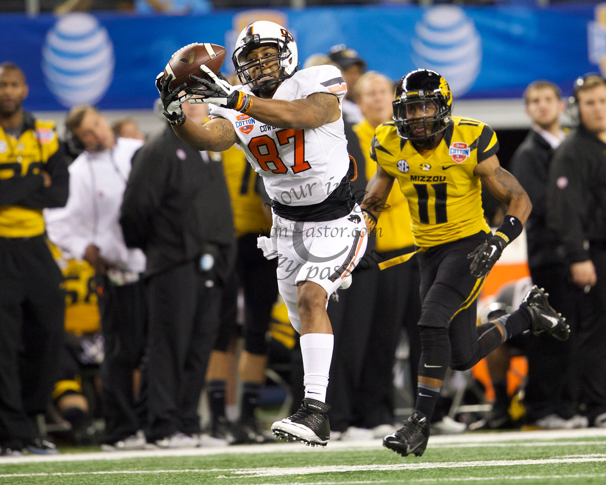 Oklahoma State senior wide receiver Tracy Moore (87) stretches out to make a first down reception in front of Missouri defensive back Aarion Penton late in the 4th quarter at the 2014 AT&T Cotton Bowl Classic in Arlington Texas. Missouri won the game 41-31.