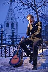 "SAMIR - Moscow, Russia  I was lying down in the snow for much of this set to get the angle that I wanted, but at least I had a coat on: it took Samir a while to thaw out once we got back inside.  I switched the camera's white balance to tungsten to accentuate the twilight sky, which was already blue, and lit Samir with one bare speedlite on a stand camera left, double gelled with CTO filters to simulate the warm glow of a streetlamp.  I tried using an umbrella at first but a gust of Moscow's winter wind quickly blew my flash over into the snow, even with my camera bag weighing down the lightstand.      This shot isn't as ""edited"" as it looks.  The colors are pretty much identical to the original, aside from a touch of desaturation to minimize clipping.  Although I did spent quite a lot of time in photoshop working on this photo, trying all sorts of different approaches, many of which were quite dramatic, this was one of those times when almost nothing I did seemed to significantly improve the shot, and frequently made it worse.  I ended up fading the opacity of nearly every layer down so low that it was barely noticeable.  The finished result has a little bit more sharpness, a little less noise, a little more mid-tone contrast, and lighter shadows.  Overall it's an improvement, but really not much different from the original.  Hopefully that's good enough."