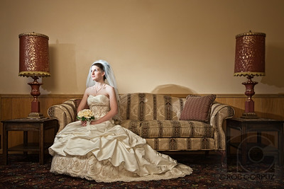 KATE ON THE SOFA - Titusville, PA, USA  This is one of my favorite individual shots of Kate in her wedding gown.  The lighting included a speedlite in an umbrella as the key, a snooted flash to add a touch of light just to her face, and an on-axis strobe in a ring-light attachment to provide some overall fill.  All the lights had various degrees of CTO gels attached to add some warmth to the room.  I did some significant editing here: lens distortion correction to straighten out vertical and horizontal lines, some contrast masking to emphasize detail and add mid-tone contrast, and the removal of some distracting elements: electrical cords, the edge of a door frame, and a painting hanging on the wall, which in later shots I physically took off the wall but I really loved her expression in this particular frame, so I decided to go with this one even if it meant some extra photoshop work.  Now I also wish I had taken the lamps out of the shot, and I thought about trying to do so in photoshop, but decided that, with the shadows they cast, it would just be too difficult.