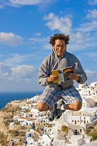 READING IS FUN - Santorini, Greece  It took a really long time and many, many tries to get this photo.  The next day we happened to be back in the exact same area (up at a fort on a cliff), and due to a very strong wind this shot would have been impossible at the time, since it required him jumping off of a wall overlooking a very steep drop.