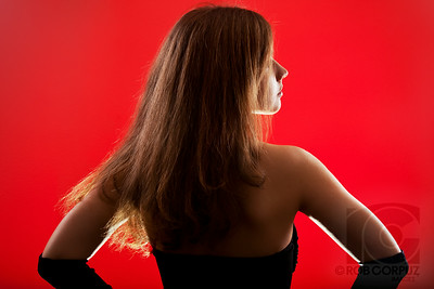 LADY ON RED  Lighting: two monoblocs with double layers of red gels cross-lighting the background wall, one monobloc directly behind her (relative to the camera) with no modifier to give a low rim light, two speedlites at about 10 and 2 o'clock providing kicker, and an on-camera speedlite in a big bounce giving some very light fill.  Post: a bit of retouching just to smooth things out a bit, taming a highlight on her arm and a small shadow on the wall, along with a little added contrast and a tiny boost in saturation.
