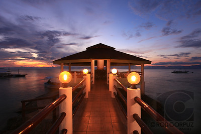 PIER - Moal Boal, Philippines  For this (unedited) shot I put one strobe at the end of the pier to light up the inside of the roof and held out one over the water off-camera right.  Both had CTO gels.  See more from the Philippines here.