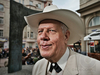 "MORE THAN MEETS THE EYES - Moscow, Russia  An outfit consisting of a cowboy hat, creamy-white suit, and crossover tie would stand out pretty much anywhere in the world except Texas.  In Moscow however, this is a fashion statement roughly comparable to walking down Main Street, Smalltown, USA wearing a knight's shining armor.    So when I saw this distinguished-looking cowboy standing across the street, apparently waiting for an appointment (a correct guess, as it turns out, although the guy never did show up), I figured anyone wearing those clothes in Russia would have an interesting character that might come through in a photo, so I decided to ask him for one.    Having just sat down with a friend at a restaurant, I pulled my camera and a flash out of my bag just as he started wandering off, chased after him, and then realized that my flash had no batteries.  Nice.  I quickly sped back to my bag for more, and went off again in search of him, hopeful that he would be fairly easy to spot in a crowd (another correct guess).  I asked him, in Russian, if I could take a photo of him, fully expecting him to respond in an American southern drawl, but this time I was wrong, as he turned out to be Russian.  I was, however, right in suspecting that he'd have an interesting story.  Serzh is an ""extreme artist,"" whose various skills include performing illusions and magic, hypnosis, as well as dangerous and sometimes death-defying stunts, such as pounding nails into wood with his bare hands, being voluntarily choked with ropes, and driving really fast while blindfolded.    I invited him to join me and my friend for a drink, and in no time at all he was doing card tricks, untying scarves that my friend had tied himself, and guessing what objects patrons of the restaurant were holding while blindfolded (and yes, we tried the blindfold ourselves).  While he didn't want to perform anything dangerous in the restaurant, he promised to do so later.  Since he's been doing this for over thirty years, I assume he's good at it, although he admitted to making a very bloody mistake once with the nail trick.  Serzh is easily one of the most unique and fascinating characters I've ever had the good fortune to meet, dripping with charm and charisma, with twinkling eyes that invite or perhaps hypnotize you into wanting to believe him when he assures you that while some parts of his act are mere illusions, others are only possible by using powers that few eyes can see.  Even if it's all misdirection and skilled sleight-of-hand, there's undeniably something magical about Serzh.    Photography may not be quite as, well, flashy as driving while blindfolded, but for me, the creative process of taking a heavy chunk of metal, plastic and glass and trying to make a flat rectangle of little dots that can somehow please the eyes, fire up the mind, and move the heart of a viewer requires another kind of wizardry, and is something well worth looking into.  And you might just transform a stranger into a friend in the process.  That's definitely magic.             I shot this with one bare speedlite handheld camera-left and up, pointed to focus attention on his remarkable face.  There is some photoshop work as well, but I hope that it isn't obvious unless you look closely."