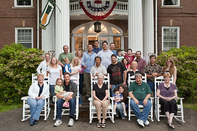 "THE FAMILY - Titusville, PA, USA  At every family reunion, in spite of the fact that many, if not most people, aren't particularly fond of getting their photo taken, at some point, everyone will agree to pose for a group photo.  We do this because we know, deep down inside, there is value in it.    At the time this was taken, our beloved matriarch Margie could not be present because of her health, and the newest member of our family tree was yet to be born, and because of this, for a while I thought I wouldn't bother with putting in the effort to edit and share it, but now I understand that it's important, because any particular photo of your family will inevitably only capture that particular moment, and not only is it totally okay that people are missing from it, but it's right and proper.  A family's line is forever being altered:  Branches fall away and and grow again in other parts of the tree, and this is the way it should be.  The point is that the tree keeps growing.    This is one of the reasons I believe that no matter how prevalent video becomes, still photography will never die.  If there's one thing that humans have been unable to truly change, it's that time marches on.  Moments are fleeting.  Still photos do something better than no other medium can: freeze one particular moment for as long as someone should care to look at it.  While the real world moves onward relentlessly, a photo can always take you back to one particular point in time and space, and remind you both of everything that built up to that moment, as well as carry all of the kinetic energy of what would come to pass.  A photo does something that human eyes can't: stop time.    At this particular time, I was the photographer, and later, I learned something very, VERY important about photographing groups from shooting this: TAKE LOTS OF FRAMES.  THEN SHOOT MORE.  And then take a couple more, just in case:)  I thought I had already learned this lesson before, but I really had it drilled home this time, and ended up paying for it in post-production, because after going over the shots later, I realized I didn't have ONE SINGLE SHOT that met the following criteria:   1) everybody's eyes are open 2) nobody was making a stupid face that I knew they would hate 3) all of the lights popped  As a result, I ended up spending a shockingly massive amount of time combining two different photos to create the shot you see above.  Did it work?  I think so.  I doubt that anyone looking at this shot would be able to tell that of the 27 people pictured here, 18 are entirely from one photo, 7 are entirely from another, and two have heads from one and bodies from another.  And I am willing to bet that NOBODY could accurately tell me who's who.  If you think you know, send me a message or add a comment.  I'll even show you the original, full-size shot, upon request, if that will help.  For the first person who can tell me correctly (who DOESN'T have access to the original files), I promise to either buy you a reasonably nice dinner (if we can arrange it), or photoshop something for you, or write on your Facebook wall these exact words: ""You are clever and awesome and attractive and I worship the ground you walk on.""    Was it worth the effort?  Well... yes.  Because it's family.  However, that doesn't mean I would not have vastly preferred taking one shot that worked on its own instead of spending hours painstakingly molding two shots together.  So how could I have made things easier for myself?  Sure, everything seemed fine and dandy when I was looking at the little 2.5 inch screen on my camera at the time, and the hard truth for a photographer is that you rarely have the luxury of asking all of your subjects to wait around while you scrutinize each and every shot, zooming in on each and every face to make sure everything's okay.  And even if you could, the chances of you getting nice, natural smiles after everyone has started to wonder what's taking so long isn't very good.  So what's the solution?    Take as many frames as you can, while keeping the recycle time of your lights in mind, and save your best, smile-inducing, photographer jokes until after you've already popped off some frames, so that just when the energy is starting to fall a bit, you can drop some witty remarks and squeeze out a few more great smiles.  Depending on all sorts of factors (the light you have available, the gear you've got handy, the juice level of your batteries, how high you're willing to go with ISO) your recycle time can vary wildly.  And while it's likely that you won't have as much control over it on any particular shoot as you would like, you should still be aware of it, so that you can compensate.  If you're recycle time is 1.5 seconds, then keep that in mind and when you're in the thick of things, use an average joke that you already know will only net you mediocre smiles, snap the shutter, and then time everything so that you can go for the gold with your winner comment and be ready to click 1.5 seconds after your last shot.    Ideally, I'd love to shoot in a studio with outlet powered lights, so I can set my ISO at 100, choose any aperture I desire and still shoot at 1/200 shutter speed or faster, any time I want.  Unfortunately, the reality is that this often doesn't happen, and you have to pick the best compromise for your particular situation.  In this case, I was lucky because it was an overcast day.  Wait a minute, you say, isn't it better for photos if it's a beautiful sunny day?  Well, the thing is, that's not as easy a question to answer as you might think.  If you're shooting a group of people, and you're shooting outdoors, and you don't have the option of getting everyone in the shade, then an overcast day is DEFINITELY better.  A sky filled with clouds creates a natural softbox, far better than any every made by humans, sending beautifully soft light all over your subjects.  There are no harsh shadows, nobody is squinting from direct sun, and everything fits within the dynamic range of your sensor without any clipping.    However, this can also flatten the contrast of your shot, which means you might want to add some additional light to create more shape and depth for your subjects.  That's what I was trying to do here.  I had one speedlite activated on-camera, to provide some fill for eyes that would otherwise be shaded within their sockets, a speedlite in an umbrella to add some pop and depth (""feathered"" toward the the farthest people from the light), and one sitting inside the building on a chair to light up the interior and provide some separation light as well as a bit of atmosphere.  It may have been in the thick of summer, but in photos it often helps to add some warmth to your interiors, regardless of the outside temperature.  Without that light inside, the interior of the building wouldn't factor as much into the picture.  With that inside light, I like to think that the viewer will subconsciously imagine everyone being welcomed back indoors after the photo is done for a coffee or a hot cocoa.  Even if I really think about it, I can't remember what happened right after we shot this.  I can't recall if we went in for coffee and cocoa or if we went home.  However, I do remember the overall feeling of the occasion, which was warm and fuzzy and soft and welcoming and happy and precious, and that's what I wanted to get across here.  It was the feeling of something special happening, of people connected by blood who had gathered from various parts of the world to be in one particular place at one particular time, to revel in the life-affirming event of marriage.    Those feelings of holding hands, of hugs all around, of embracing our past and our future, are all worth capturing.  And you know what?  Even during those family occasions where everyone is tired and irritated and debating different politics and clashing on generational issues, those are worth capturing too.  It's all part of the journey.  Just as we've all stared in wonder at old photos of our ancestors, we owe it to our descendants to do the same for them, if for no other reason than to give them something to remember us by other than those embarrassing videos of us that will forever be on available on YouTube."