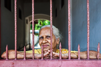 WOMAN BEHIND A GATE - Cochin, India  I should've changed the camera angle slightly so that one spike didn't look like it was going up her nose.  Oh well.  I may come back to this later and change it.  EDIT: So I did change it, shortening the tip of the spike under her nose so it wasn't quite as distracting, as well as making the whole photo pop a bit more.