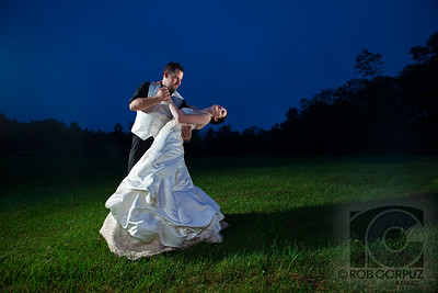 "A BREAK FROM THE RECEPTION - Titusville, PA, USA  I managed to steal the bride & groom for a few minutes from the reception right as ""magic hour"" was coming to a close.  Got that blue in the sky by setting the camera's white balance to tungsten and using CTO gels on the three speedlites to compensate.  It had just been raining and, as much as I wanted to avoid it, the only way I could get the angle that I wanted was by sitting down in the mud.  However, since I was already totally and repeatedly drenched in sweat and grime from spending a hectic summer's day lugging two heavy bags of photo equipment around with two cameras hanging permanently hanging from my neck, the mud was probably more grossed out by having to touch me than the other way around:)  May have to redo the post-processing on this one to try and eliminate the banding in the sky.  This was taken from a RAW file, processed 16 bit, and, after I saw the banding the JPG, I masked out almost all the edits I did to the sky: it's basically exactly how it was in the original, but I'm assuming I made a mistake in terms of color space and will have to do it all over again.  Grrr..."