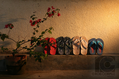 "FLIP-FLOPS - Cebu, Philippines  One amber gelled strobe on manual off-camera right zoomed to a narrow beam and angled down to simulate sunlight peeking through.  Note: apologies to all folks from Hawai'i who may be upset that I didn't entitle this photo ""Slippas"" rather than ""Flip-flops.""  Unedited."