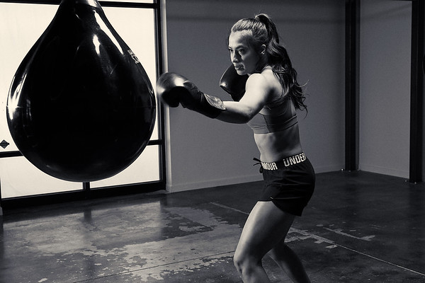Female Boxer hitting bag in Gym