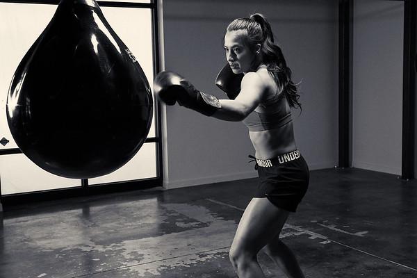 Female Boxer hitting bag in Gym