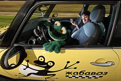 """FROG TAXI - Usovo, Russia  The Cyrillic on the side of the car tranlates, literally, to """"toad carrier.""""  In Russia, """"toad"""" is a slang term for what Americans would call a """"gold digger.""""  I'm going to divulge a big secret here: Frog isn't a real cab driver!  He is, in fact, the first professional model I've worked with.  Thanks also to Richard (the passenger), for helping out pro bono and being willing to make goofy, no-so-flattering faces in the name of photography.  Frog, on the other hand, simply will not allow his likeness captured without a ton of make-up caked on, and he refuses to make any other expression other than his trademark """"Green Steel"""" look."""