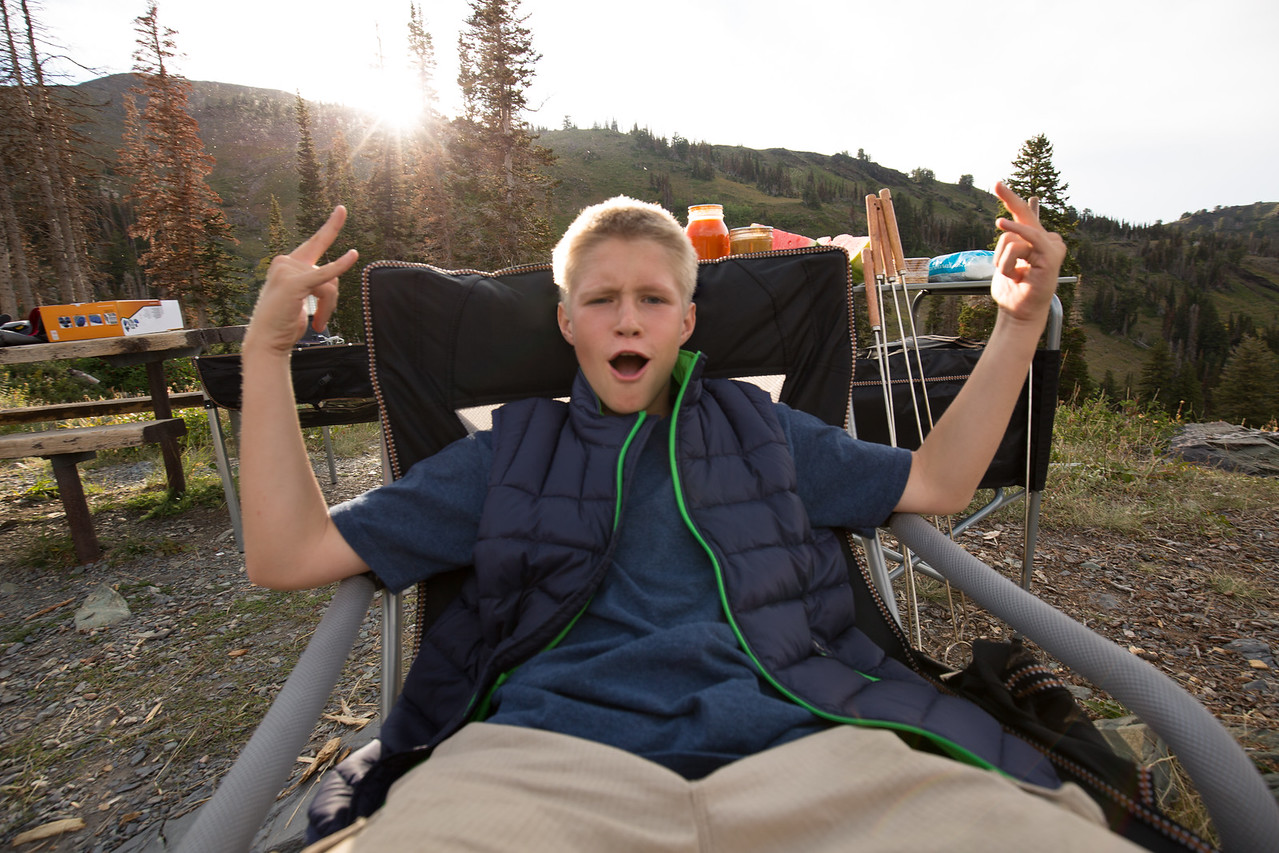a teenage boy sitting in a camping chair, excited