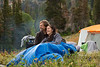 a husband and wife snuggling in a sleeping bag at a campsite