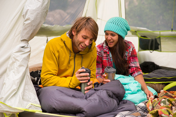 a young couple camping and enjoying coffee in a tent