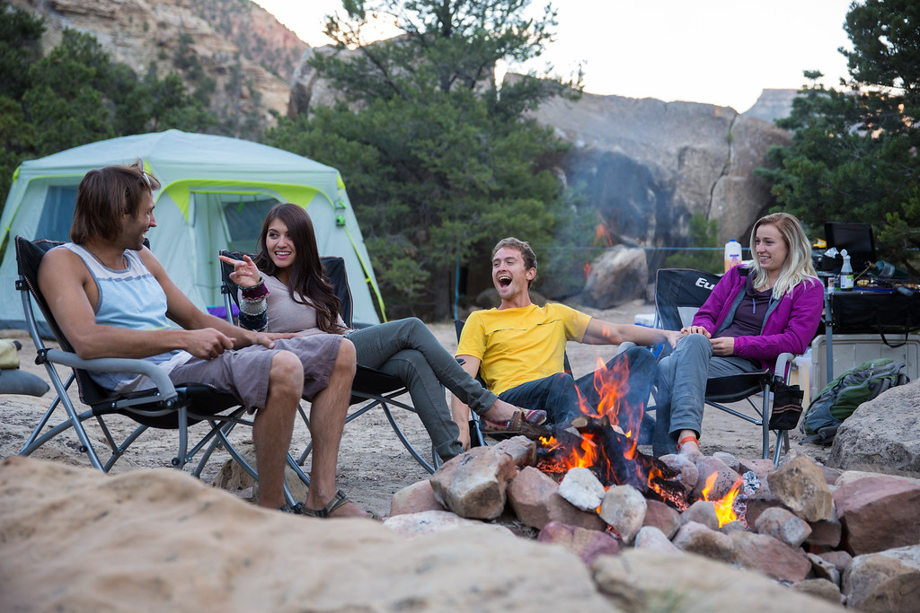 a group of four friends camping and laughing by a fire