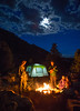 four friends camping and playing ukulele by a fire