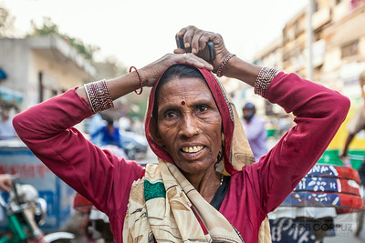 WOMAN - Delhi, India  This lady had her arms above her head, staring thoughtfully off into the distance, and when I asked her for a photo, she immediately brought her arms down.  I asked her to put them up again, to try and duplicate the way she had been standing naturally, but it wasn't quite the same.  If I'd had a telephoto lens on the camera at the time, I probably would've taken a candid shot first, but since I had a wide-angle lens attached (purposefully, to allow a more intimate feel the shots), I would've had to be pretty sneaky to get a candid photo.