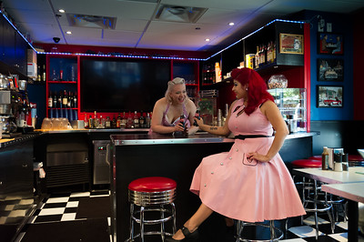 Two pinup girls having fun at a retro restaurant.