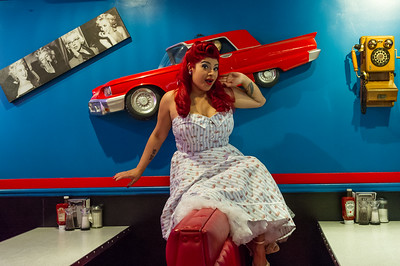 Pinup model sit on booth in restaurant