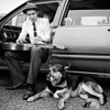 Douglas Francisco, a musician from New Orleans, plays his 1932 dobro next to his dog, Pancho, as he awaits his turn to go onstage during the Red Devil Festival in Elkmont. Francisco travels with Pancho all over the Country performing his solo act. Frequently he sleeps in his car to save money.
