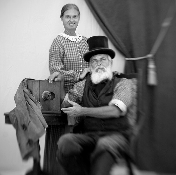 "Wendell R. Decker, seated, from Bowling Green, Ky., takes period pictures with a ""sliding box"" camera from the 1850's (on the left). The camera hasn't been modified and Decker uses the same technique used during the Civil War. He travels with assistant Suzy McGill (standing) from one Civil War reenactment to the next one taking pictures of both reenactors and the public.<br /> Note: This portrait was taken using a ""lensbaby"" during the reenactment of the Battle of Decatur, Alabama."
