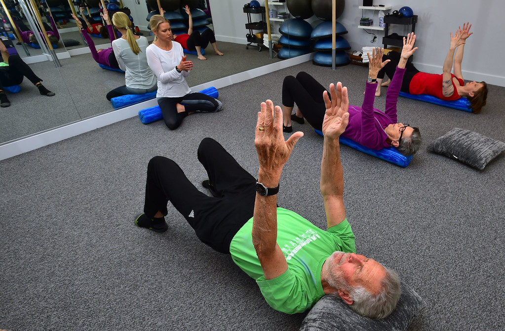 . Instructor Heli Ananda leads Dan Luecke and Rosemary Wrzos in a spine warmup in the Body Dynamics mend Posture Perfect Class in their Boulder facilities on Wednesday.  For more photos go to www.dailycamera.com Paul Aiken Staff Photographer April 12, 2017