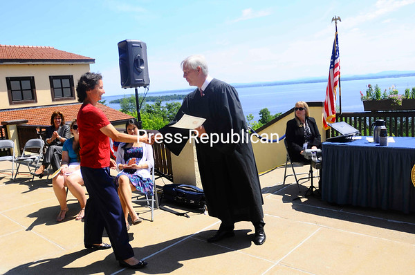 Friday, July 8, 2011. Naturalization ceremony held by Clinton County Supreme Court at Clinton Community College. Justice of the Supreme Court John Lahtinen presided, along with Immigration Officer Lawrence Clancy and Clinton County Clerk John Zurlo Sr.<br><br>(Staff Photo/Kelli Catana)