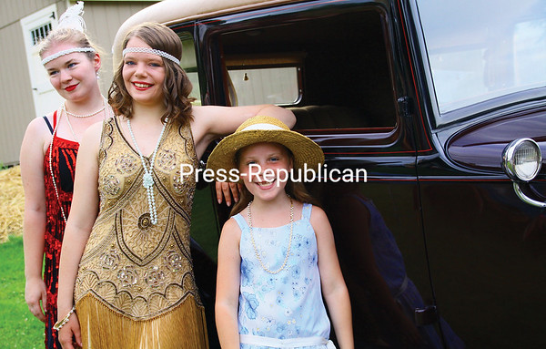 ALVIN REINER/P-R PHOTO Though not as elderly as the antiquated vehicle they pose with, Shelby Spaulding (left) and sisters Eliza Strum (center) and Mackenzie Strum could very well be taken as residents from the Roaring '20s.