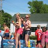 Emily Provost (right) stands atop the Cool Summer Fun Float at the 4th of July Parade in Hinesburg, VT