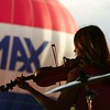 Sophie Severance, the violinist for the band Middle Ground, plays as the RE/MAX hot air balloon inflates during the opening night of the Mayor's Cup Festival at Plattsburgh City Beach.