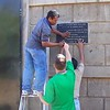 James Carlin (center) assists Chico and Rene in mounting our new plaque outside our gate - where the people of the barrio asked to have it placed.
