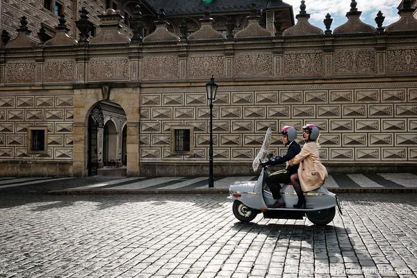 PRAGUE. Decouvrir Prague  ( ici la place Hradčany ) au guidon d'un vespa de l'est: le Čezeta. Des passionnés ont relancé le modèle de 1957 en l'équipant d'un moteur électrique. L'Hotel Josef propose en exclusivité à ses clients une échappée gratuite de trois heures.