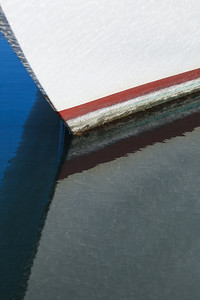 Graphic detail of bow of boat and reflection.