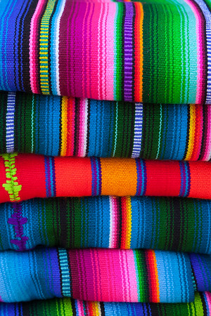 Colorful stack of hand-woven textiles.