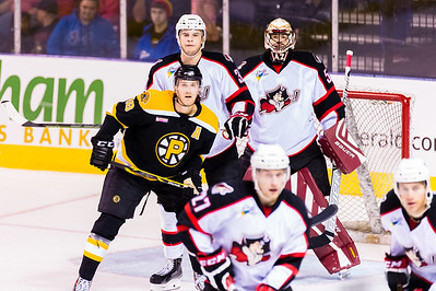 Justin Florek #18(LW) of the Providence Bruins battles for a screen in front of Mark Louis #33(D) of the Portland Pirates and Mike McKenna #56(G) of the Portland Pirates during the Portland Pirates 2014-15 season opener vs the Providence Bruins at the Cross Insurance Arena in Portland, Maine on 10/11/2014. (Photo by Michael McSweeney/Portland Pirates)