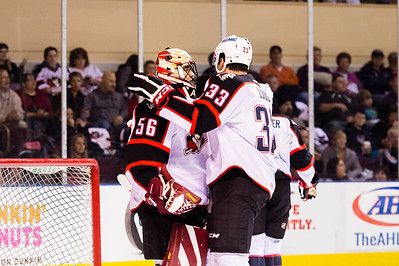 Mark Louis #33(D) of the Portland Pirates congratulates Mike McKenna #56(G) of the Portland Pirates after an unbelievable save during the Portland Pirates 2014-15 season opener vs the Providence Bruins at the Cross Insurance Arena in Portland, Maine on 10/11/2014. (Photo by Michael McSweeney/Portland Pirates)