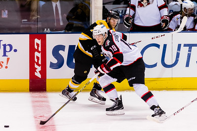 Henrik Samuelsson #19(LW) of the Portland Pirates dekes around Joe Morrow #7(D) of the Providence Bruins  during the Portland Pirates 2014-15 season opener vs the Providence Bruins at the Cross Insurance Arena in Portland, Maine on 10/11/2014. (Photo by Michael McSweeney/Portland Pirates)