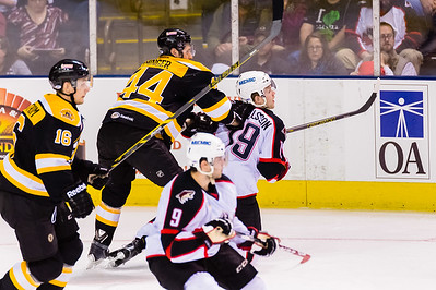 Steve Eminger #44(D) of the Providence Bruins finishes a check on Henrik Samuelsson #19(LW) of the Portland Pirates during the Portland Pirates 2014-15 season opener vs the Providence Bruins at the Cross Insurance Arena in Portland, Maine on 10/11/2014. (Photo by Michael McSweeney/Portland Pirates)
