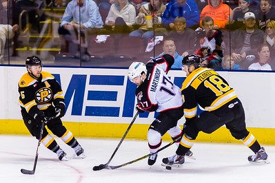 Justin Florek #18(LW) of the Providence Bruins deflects a puck with his skate as Jordan Martinook #17(C) of the Portland Pirates tries to receive a pass during the Portland Pirates 2014-15 season opener vs the Providence Bruins at the Cross Insurance Arena in Portland, Maine on 10/11/2014. David Warsofsky #5(D) of the Providence Bruins also pictured. (Photo by Michael McSweeney/Portland Pirates)