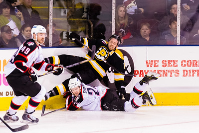 Brendan Shinnimin #24(C) of the Portland Pirates crashes in to David Warsofsky #5(D) of the Providence Bruins during the Portland Pirates 2014-15 season opener vs the Providence Bruins at the Cross Insurance Arena in Portland, Maine on 10/11/2014. (Photo by Michael McSweeney/Portland Pirates)