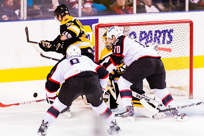 Zach Trotman #37(D) of the Providence Bruins tries to clear the puck in front of Jeremy Smith #30(G) of the Providence Bruins while Jordan Szwarz #10(RW) of the Portland Pirates and Tobias Reider #9(C) of the Portland Pirates apply pressure during the Portland Pirates 2014-15 season opener vs the Providence Bruins at the Cross Insurance Arena in Portland, Maine on 10/11/2014. (Photo by Michael McSweeney/Portland Pirates)