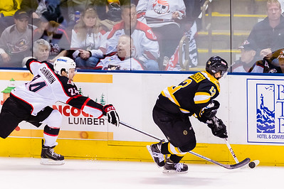 Alexander Khokhlachev #13(C) of the Providence Bruins looks to send the puck up ice as Brendan Shinnimin #24(C) of the Portland Pirates closes during the Portland Pirates 2014-15 season opener vs the Providence Bruins at the Cross Insurance Arena in Portland, Maine on 10/11/2014. (Photo by Michael McSweeney/Portland Pirates)