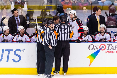 Alex Garon #64(R) explains a penalty call to Ray Edwards, Head Coach/General Manager of the Portland Pirates during the Portland Pirates 2014-15 season opener vs the Providence Bruins at the Cross Insurance Arena in Portland, Maine on 10/11/2014. (Photo by Michael McSweeney/Portland Pirates)