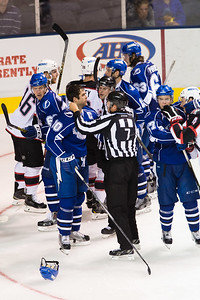 Tempers flared late as Linesman Alex Stagnone (#7) restrains Mike Angelidis #10(C) of the Syracuse Crunch  during the Portland Pirates regular season contest vs. the Syracuse Crunch at the Cross Insurance Arena in Portland, Maine on 10/25/2014. Portland Pirates won 2-1. (Photo by Michael McSweeney/Portland Pirates)