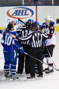 Linesman Alex Stagnone (#7) tries to keep distance between Mike Angelidis #10(C) of the Syracuse Crunch   and Andrew Campbell #4(D) of the Portland Pirates in the third period of the Portland Pirates regular season contest vs. the Syracuse Crunch at the Cross Insurance Arena in Portland, Maine on 10/25/2014. (Photo by Michael McSweeney/Portland Pirates)